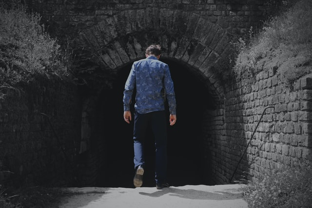 man walking into a tunnel