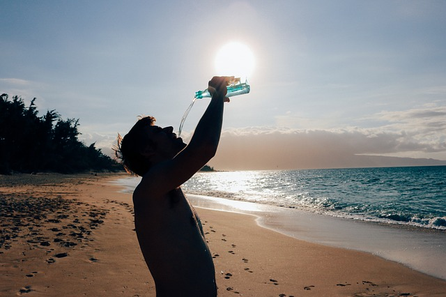 man drinking water in a beach
