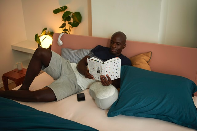 man reading at night on his bed